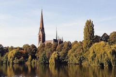 Uhlenhorster St. Gertrud Kirche am Kuhmühlenteich zwischen Herbstbäumen.