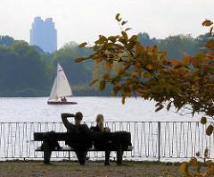 Herbst in der Hansestadt Hamburg - ein Pärchen sitzt auf einer Bank an der Alster.