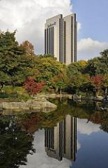 Hotelhochhaus am Dammtor - die moderne Architektur spiegelt sich im Wasser eines Sees in Planten un Blomen - herbstlich gefärbte Bäume am Ufer der Anlage.
