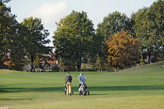 Golfplatz am Treudelberg - Golfspieler ziehen ihren Caddy über das Grün - Herbstbäume im Hintergrund.