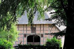 Fachwerkhaus mit Reet gedeckt zwischen Bäumen - historische Häuser in Hamburg Rönneburg.