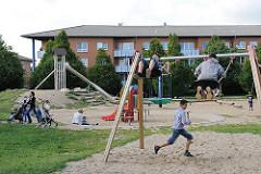 Kinderspielplatz Neuallermöhe - Jungendliche auf einer Schaukel -  Mütter spielen mit ihren Kindern im Sand.