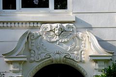 Stuckdekor / Bauschmuck mit Engel, Putte über dem Eingang eines Gründerzeitgebäudes in HH-Eimsbüttel.