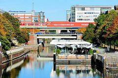 Mittelkanal in Hamburg Hammerbrook - auf einem Ponton ist ein Restaurant eingerichtet - in der S-Bahnstation Hammerbrook fährt ein Zug ein.