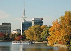 Hamburger Herbst - in Herbstfarben leuchtende Bäume stehen am Alsterufer der Binnenalster - ein Alsterschiff fährt Richtung Lombardsbrücke - im Hintergrund die Hochhäuser an der Esplanade und der Hamburger Fernsehturm / Heinrich-Hertz-Turm, Telemiche