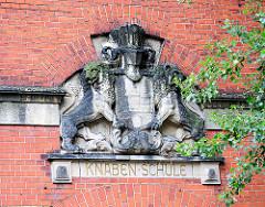 """Fassadenschmuck an der ehem. Volksschule Telemannstrasse in HH-Eimsbüttel - Löwen halten das Wappen der Hansestadt Hamburg - Inschrift darunter """"KNABEN SCHULE""""."""