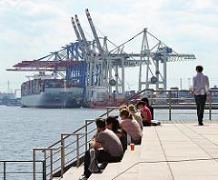 Mittagspause in der Altonaer Altstadt - Menschen sitzen auf einer Treppe in der Grossen Elbstrasse - im Hintergrund das Tollerort-Container Terminal im Hamburger Hafen - ein Frachter liegt unter den Containerbrücken.