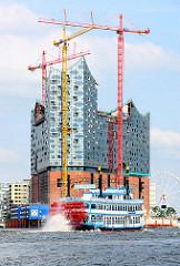 Baukräne an der entstehenden Elbphilharmonie - ein Raddampfer der Hamburger Hafenrundfahrt auf seiner Fahrt durch den Hafen.