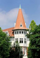 Turmerker mit spitzem Dach - Turmfenster; Gebäude im Grünen in Hamburg Bahrenfeld.