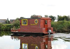 Hausboot in Fahrt - Kahn mit Holzaufbau / Holzhaus und Aussenbordmotor auf der Doveelbe vor Hamburg Reitbrook.