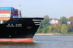 Das Container Frachtschiff HANJIN SPAIN läuft auf der Elbe in den Hamburger Hafen ein - im Hintergrund eine Villa am Elbhang an der Elbchaussee zwischen Bäumen.