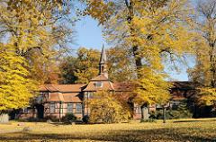 Wellingsbüttler Torhaus - Herbstbäume in der Sonne.