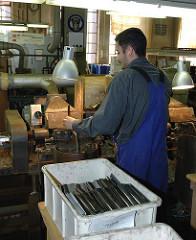 Arbeiter in der New-York Hamburger Gummi-Waaren Compagnie Aktiengesellschaft - Herstellung von Hartgummikämmen.