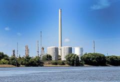 Hohe Schornsteine und Tankanlagen - Raffinerie in Hamburg Harburg am Ufer der Süderelbe.