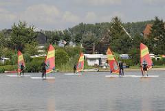 Windsurfschule am Oortkatener See. Jugendliche lernen auf dem Ochsenwerder See das Windsurfen.
