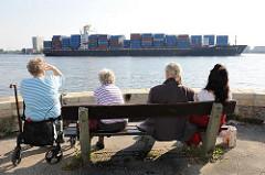 Holzbank am Elbufer - Personen beobachten das Auslaufen eines Containerschiffs aus dem Hamburger Hafen.