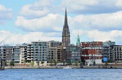 Blick über die Norderelbe zur modernen Architektur der Hamburger Hafencity - im Bildzentrum die hohe Turmruine der Nikolaikirche und rechts davon der Turm des Hambuger Rathauses.