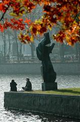 Herbst in Hamburg - rotgefärbte Ahornblätter leuchten in der Herbstsonne an der Binnenalster .