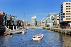 Moderne Architektur am Sandtorhafen / Traditionsschiffhafen - eine Barkasse der Hafenrundfahrt fährt in das Hafenbecken ein.