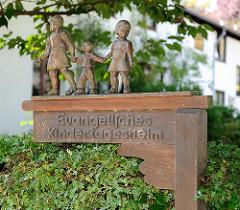 Handgeschnitztes Holzschild mit Kinderfiguren - Hinweis Evangelisches Kindertagesheim in Hamburg Nienstedten.