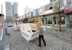 Abgesperrtes Gebiet um die einsturzgefährdeten Essohäuser am Spielbudenplatz - Ladenzeile und Container mit Sperrmüll. Im Hintergrund die Hochhäuser Tanzende Türme an der Reeperbahn.