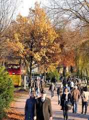 Spaziergang in der Herbstsonne an der Alster - es gehört zur Hamburger Tradition Sonntag Nachmittags einen Alsterspaziergang zu unternehmen. Auf der Strasse Schöne Aussicht fährt ein Doppeldeckerbus der Hamburger Stadtrundfahrt in dem Hamburg Tourist