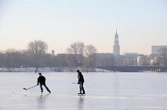 Zwei Jugendliche spielen Eishockey auf dem Alstereis.