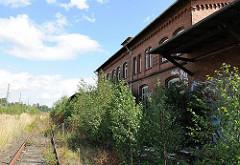 Rückseite des stillgelegten Wandsbeker Güterbahnhof - die Laderampe ist mit jungen Birken verdeckt. Der Backsteinbau steht unter Denkmalschutz.