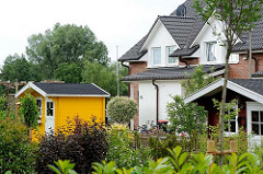 Gärten im Neubauviertel von Hamburg Langenbek - bunte Gerätehäuser aus Holz.