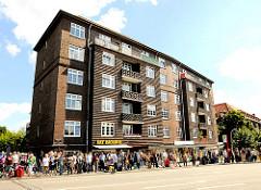 Bilder aus Hamburg Hamm - Menschenschlange an der Bushaltestelle - Wohnhaus mit Balkons.