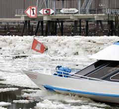 Hamburgflagge am Schiffsbug - Hafenrundfahrt im Winter - Eis auf der Elbe.