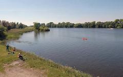 Kanu und Sportboot auf der Süderelbe - Angler am Ufer der Elbe - Naturschutzgebiet Hamburg Neuland.