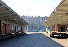 Laderampen der Zollstation Hamburg Veddel - Zollgrenze zum Hamburger Freihafen; Zollkontrolle - im Hintegrund Wohnblocks des Hamburger Stadtteils Veddel.