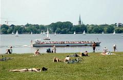 Alsterufer im Stadtteil Hohenfelde - Menschen sonnen sich auf der Wiese - ein Cabrio Alsterschiff macht mit Hamburg Touristen an Bord eine Alsterrundfahrt.