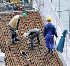 Bauarbeiter arbeiten im Juli 2013 auf dem Dach der Baustelle der Hamburger Elbphilharmonie; Vorbereitungsarbeiten an Eisengeflecht.