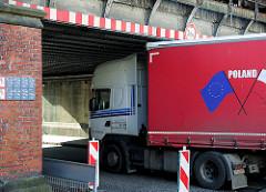 Lastwagenverkehr im Hafengebiet von Hamburg Harburg; ein polnischer LKW fährt knapp unter einer 3,80 hohen Eisenbahnbrücke hindurch.