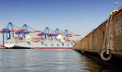 Leerer Schiffsliegeplatz im Hamburger Hafen / Ellerholzhafen; gewaltige Gummifender hängen an der Kaimauer - Containerschiff unter Containerbrücken am Container Terminal Burchardkai.