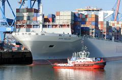 Ein Schlepper am Bug des Containerfrachters NYK HELIOS. Das 2013 gebaute Containerschiff hat eine Länge von 365,50m und eine Breite von 48,40m; der Frachter kann 13208 TEU Container transportieren.