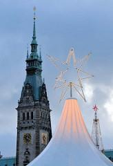 Weihnachtsmarkt - beleuchteter Weihnachtsstern vor dem Rathausturm des Hamburger Rathauses.