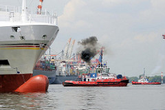 Schiffe im Hamburger Hafen - ein Schlepper stösst schwarzen Qualm aus seinem Schornstein - lks. der weit aus dem Wasser ragende Wulstbug eines Feederschiffs.
