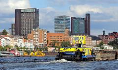 Hochhäuser an der Elbe von Hamburg St. Pauli - Hotel und Bürogebäude mit Blick auf die Elbe. Ein Schubverband fährt auf dem Fluss elbaufwärts.