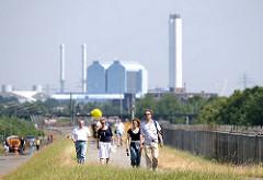 SpaziergängerInnen nutzen die neue Öffnung im Zollzaun am Wilhelmsburger Spreehafen zu einem Spaziergang auf dem Deich - im Hintergrund das Heizkraftwerk Tiefstack in Hamburg Billbrook.