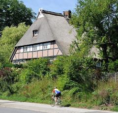 Historisches Fachwerkgebäude - Dach mit Reet gedeckt; Fahrradfahrter auf dem Fussweg - Bilder aus dem Hamburger Stadtteil Wilstorf.