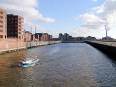 Ein Barkasse fährt im Sandtorhafen; rechts Bürogebäude, dahinter die Speicherstadt + das Kesselhaus; rechts das Kraftwerk Hafencity (2003)