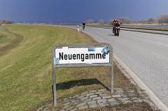 Stadtteilschild von Hamburg Neuengamme. Motorradfahrer auf der Elbdeichstrasse.