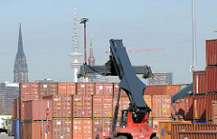 Ein Reach-Stacker greift einen Container - im Hintergrund Kirchtürme und der Fernsehturm Hamburgs. Fotos aus dem Stadtteil Kleiner Grasbrook.
