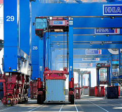 Ein Portalhubwagen transportiert einen Container unter den mächtigen Portalen der Containerkräne am Burchardkai im Hamburger Hafen.