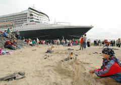 Die QUEEN MARY 2 liegt am Hamburger Kreuzfahrt Terminal / Cruise Center der Speicherstadt (2006) - Kinder spielen im Sand.