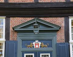 Geschnitzte Dekorelemente mit Hamburg Wappen un Löwen über dem Eingang zum Herrenhaus Wohldorf.