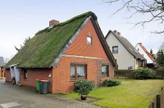Einzelhäuser mit Spitzdach in Hamburg Hausbruch - Reetdach mit Moos bedeckt - Rasen im Vorgarten.